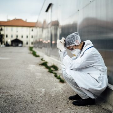 A doctor crouches down against the wall of a medical facility, overwhelmed with emotion.