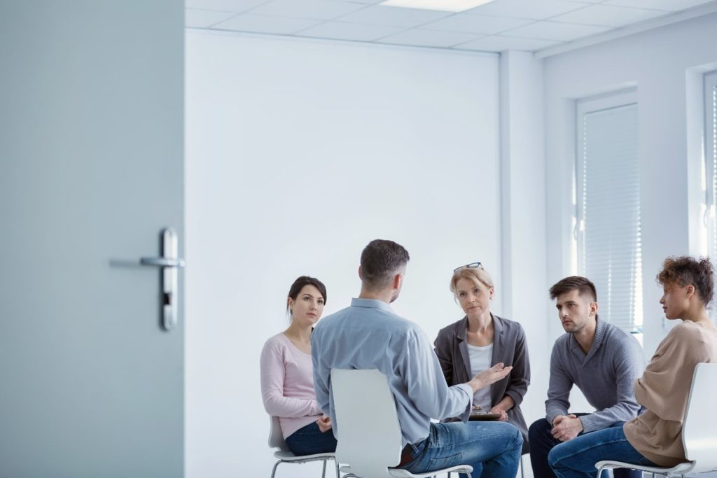 Four patients sit across from a therapist in a group therapy session for individuals suffering from PTSD